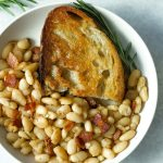 rosemary bacon beans in plate with olive oil toast