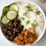 Bowl with ground beef bulgogi, rice, cucumber slices, green onion and sesame seeds
