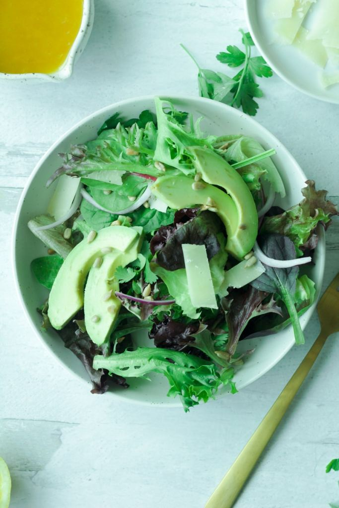 Plate of salad with greens, sliced avocado, sunflower seeds with fork on the side