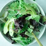 Plate of mixed salad with greens, avocado, sunflower seeds, red onion slices and dressing