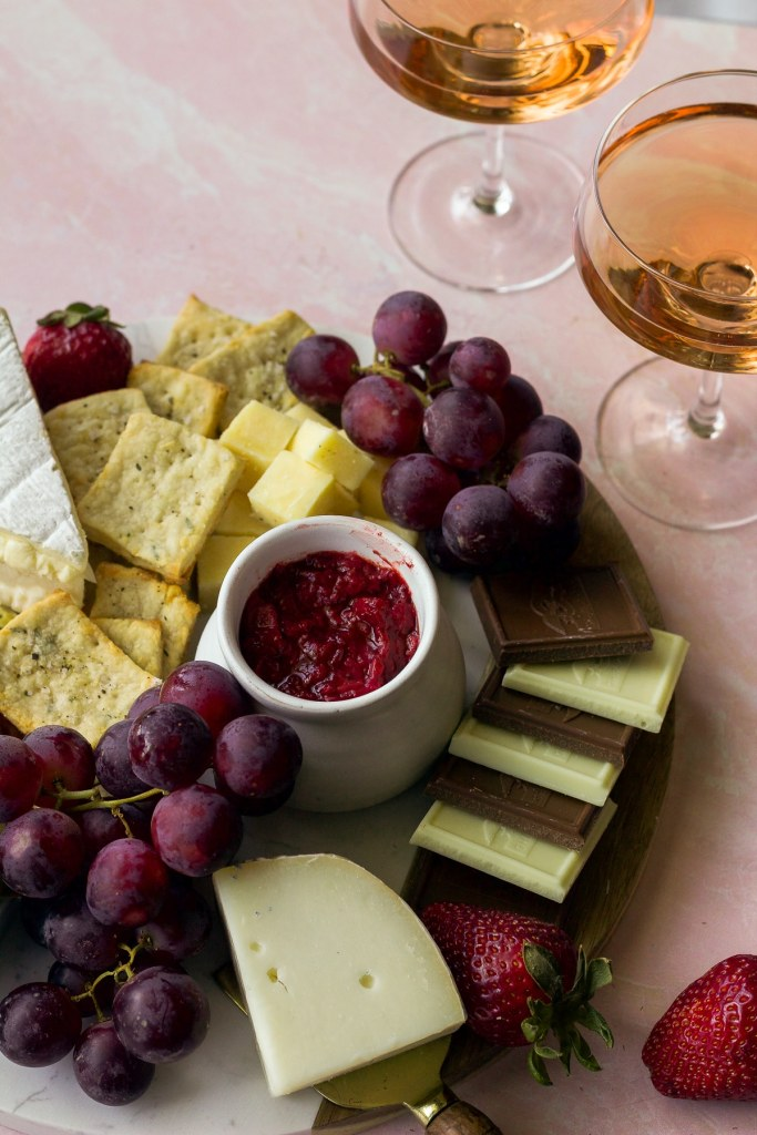 close up shot of cheese board with red grapes, chocolate bars, cheese knife and strawberries