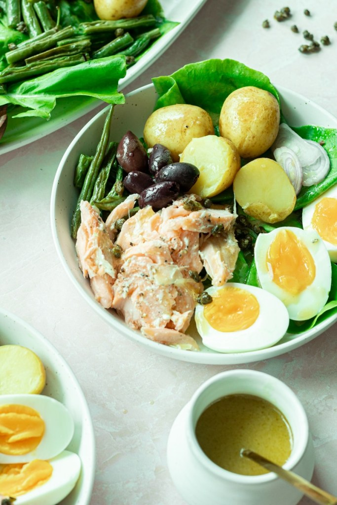 bowl of salmon niçoise salad with small jar of dressing on side