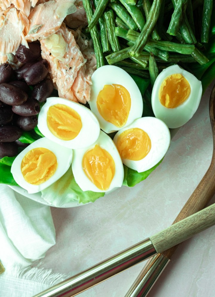 close up of soft boiled eggs in nicoise salad