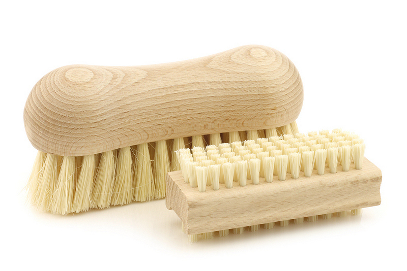 a wooden nail brush and a wooden household brush on a white bac