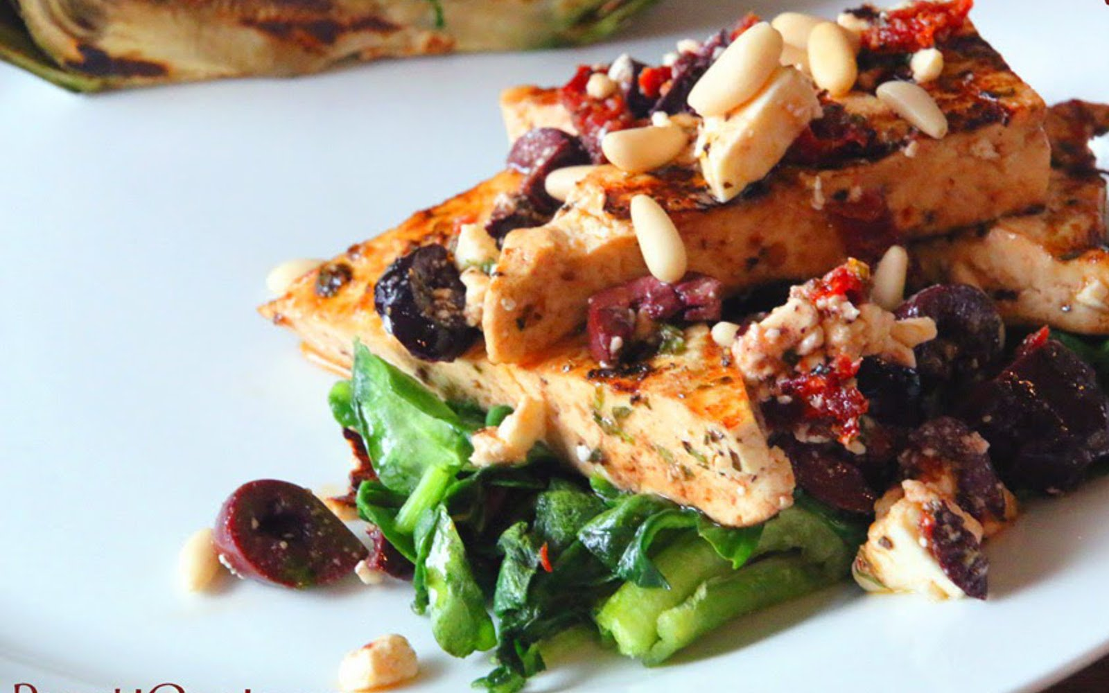 Mediterranean Tofu Steaks [Vegan, Gluten-Free] over bed of spinach with dairy-free feta and pine nut topping