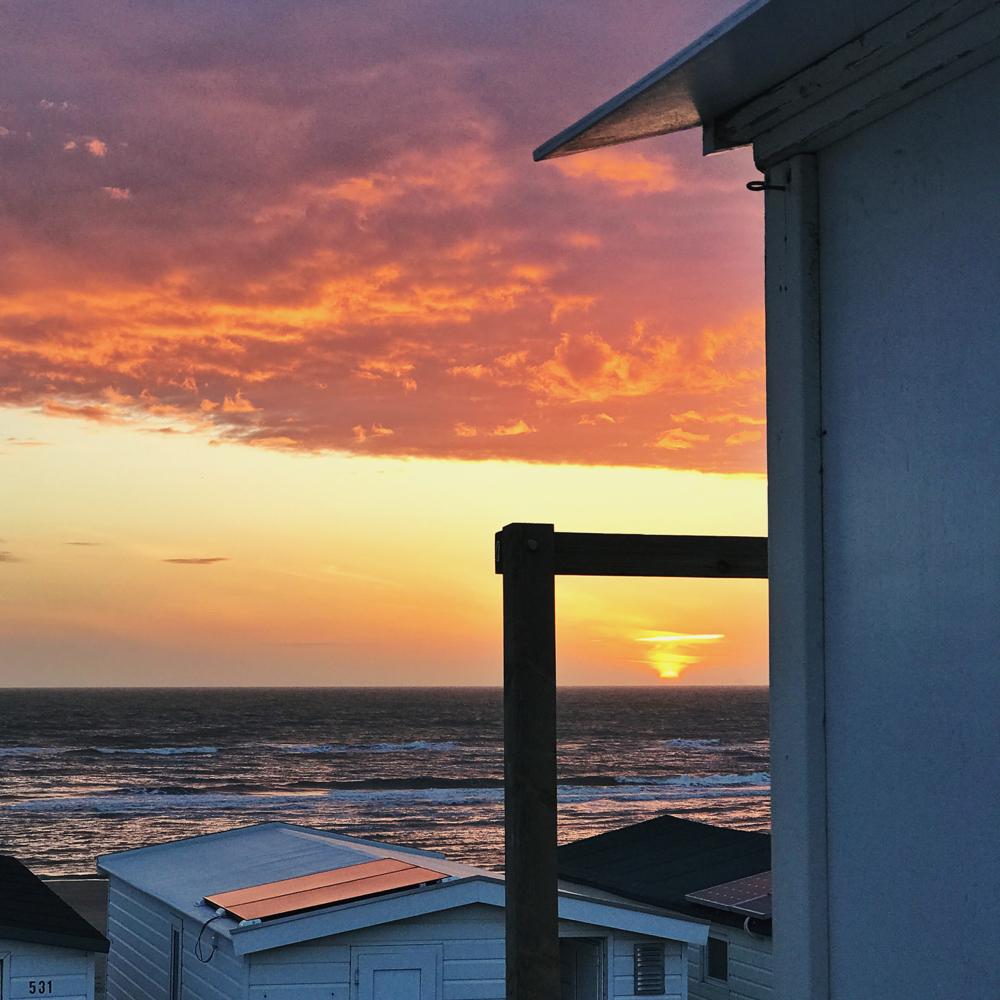 zonsondergang bij strandhuisjes