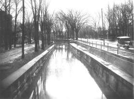 Main Street (c. 1925) The view of main Street in Oneida, looking south along the old feeder canal at Washington Avenue. The old Erie Canal feeder took water from Oneida Creek, ran parallel to Main Street in Oneida and entered the old Erie Canal near Lake Road just west of Durhamville. The City began filling in the feeder soon after this picture was taken. In the 1930s, the City built Triangle Park between Washington and Stone streets. Courtesy Madison County Historical Society, #00.60.10)