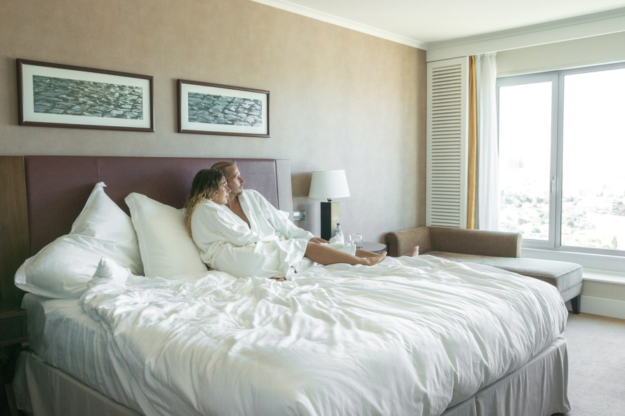 Travel couple in robes on bed in hotel room in Lisbon