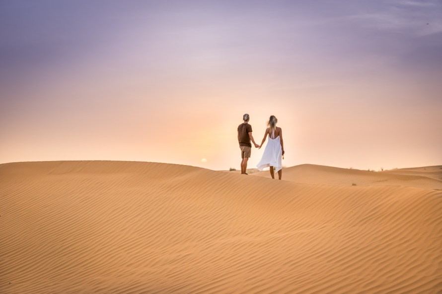 Travel couple holding hands in sand dunes Dubai
