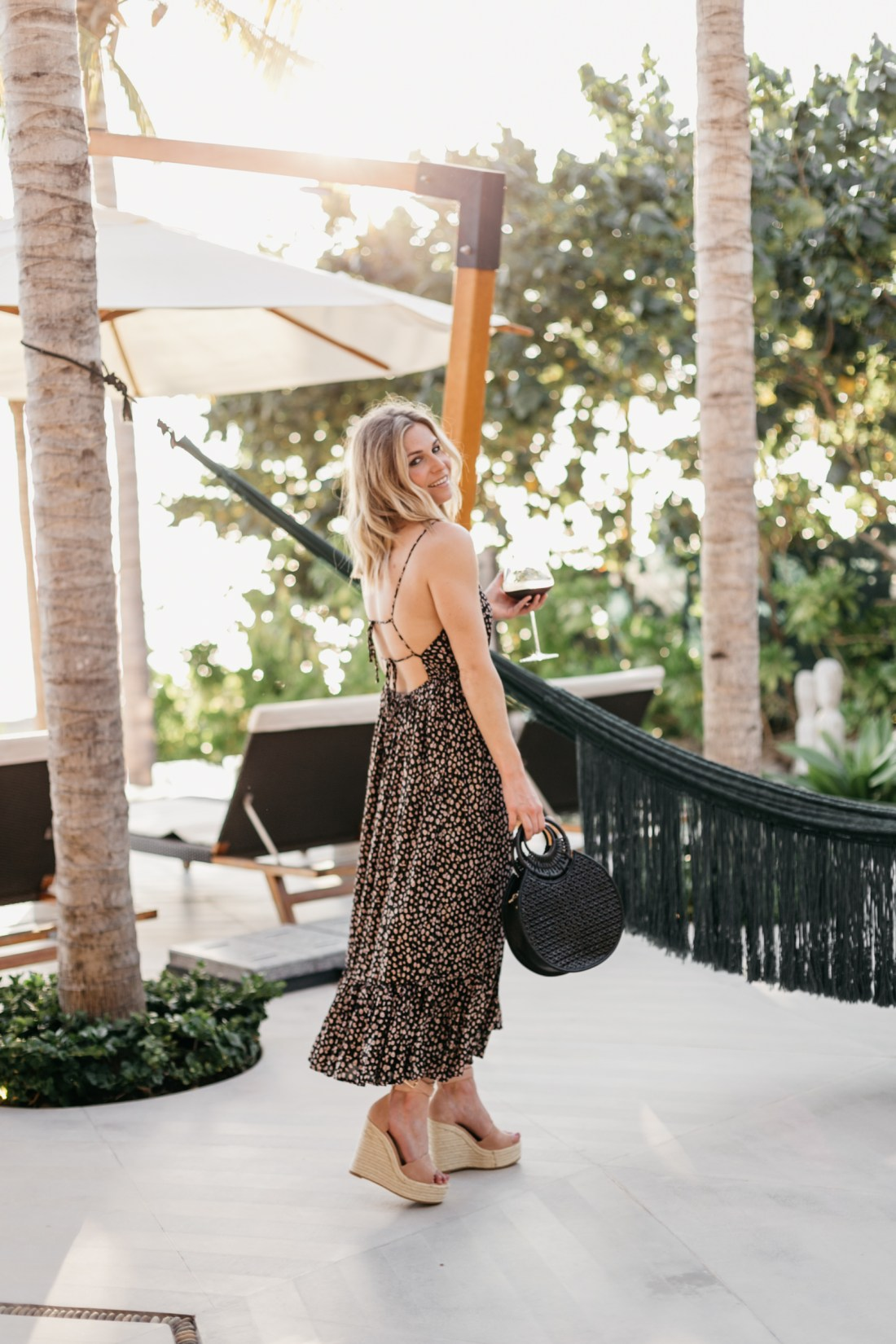 Brooke is wearing a Blue Floral Open Back Dress // Tan Strappy Wedges // Black Woven Clutch