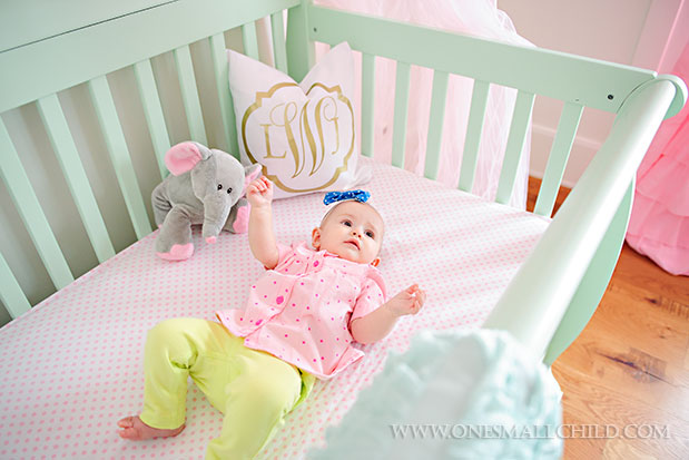 Sweet baby Lyla in her pink and aqua dream crib | See the entire nursery at One Small Child: www.onesmallchild.com