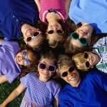 children wearing sunglasses lying with the heads together on the grass