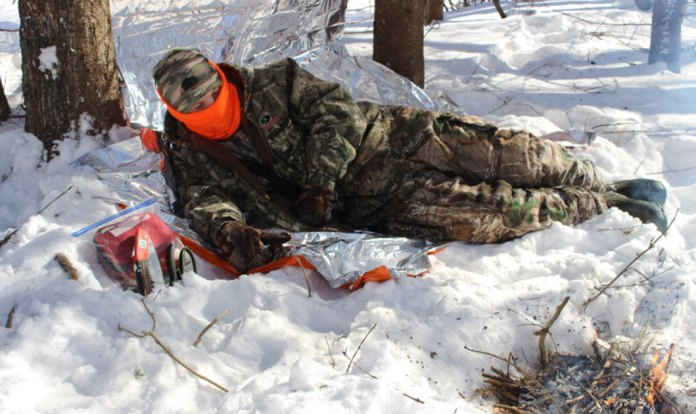 outdoorsman protected from freezing cold with shelter and fire