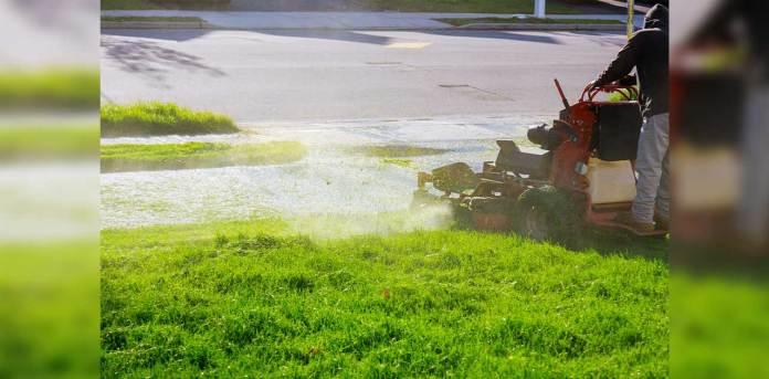 A man mows grass near his sidewalk and roadway.