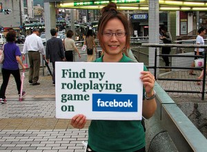 "girl holding sign saying ""find my roleplaying game on facebook"""