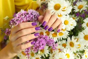 Manicure design with a matte lilac coating over a bouquet of daisies.