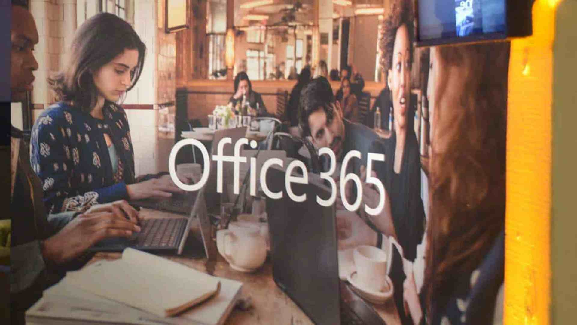 """Image of reflection on glass showing people working with Microsoft devices with """"Office 365"""" text"""