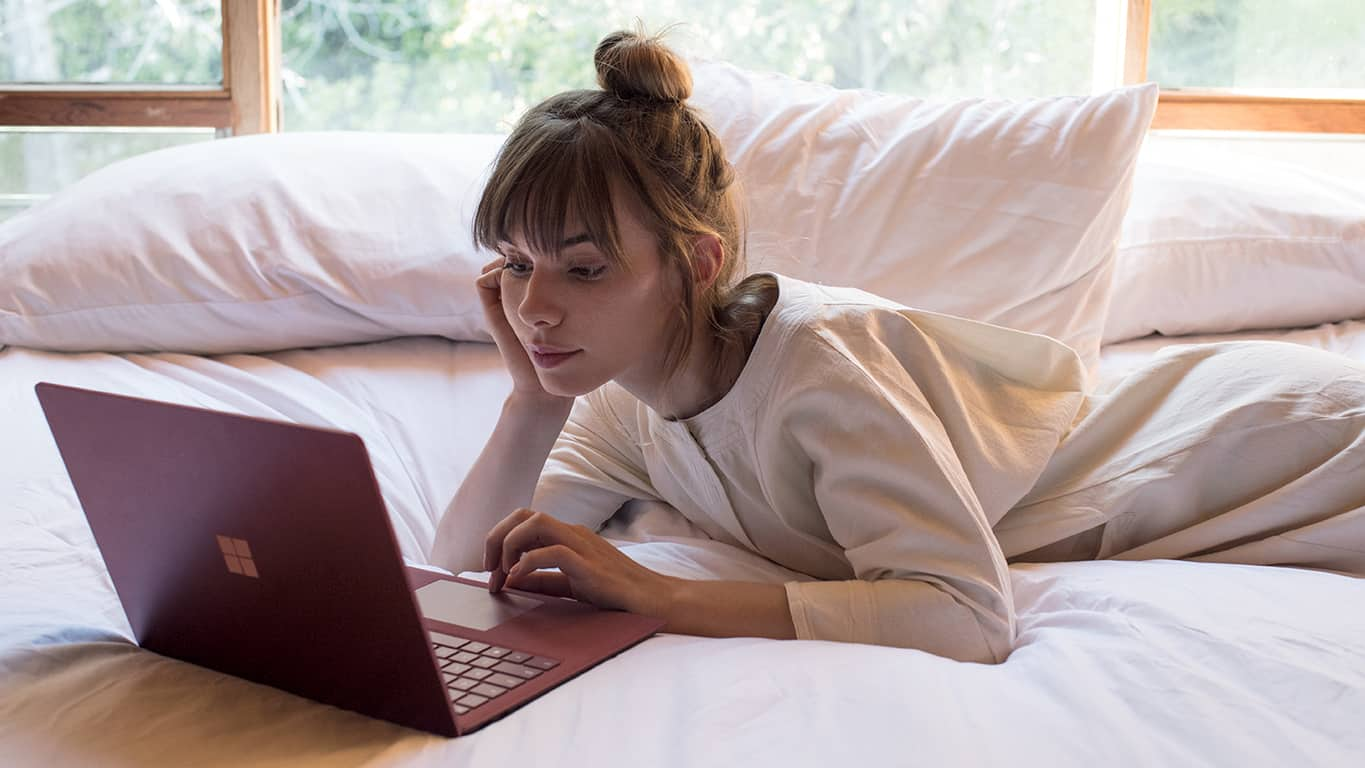 Woman reading email on a Surface on bed
