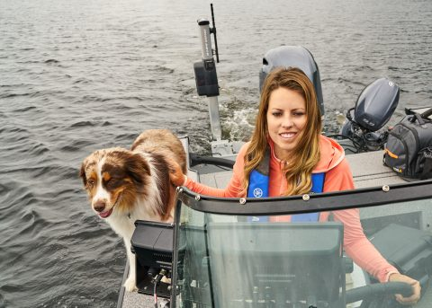 Ashley Rae drives her boat with her dog Blitz