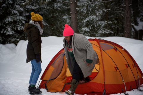 two women setting up tent while winter camping