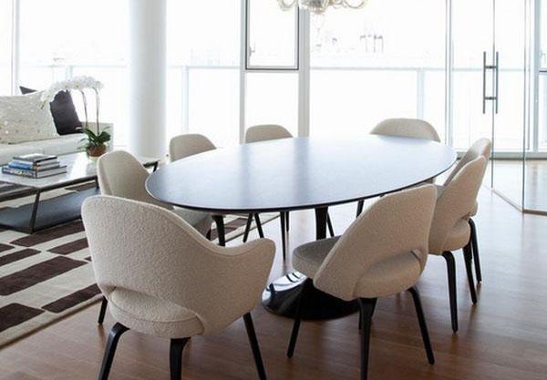 طاولة خشبية لامعة بكراسي بيضاء باهتة
