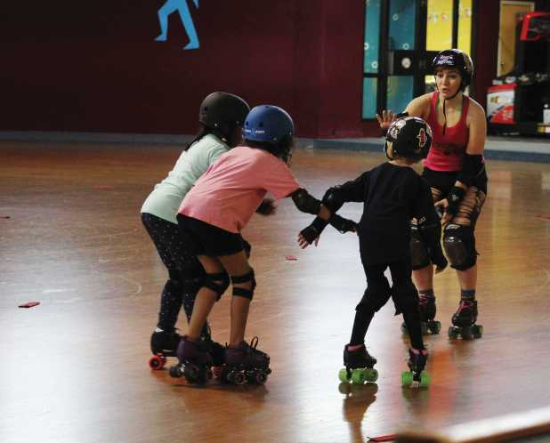 """Falling for Derby - Sophia Palmer (17, Brown) -a.k.a. """"Sockeye Slammin"""" is using her experience to teach younger girls the types of falls in roller derby. There are little things all the time that made me really glad I joined the team, Sophia said. Photo credit: Sam Sims"""