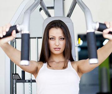 Woman Using Shoulder Press Machine