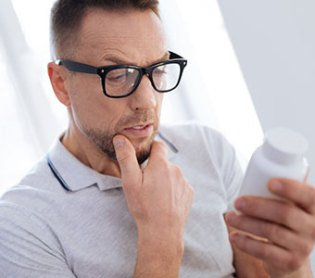 Man Thoughtfully Reading The BCAA Powder Label