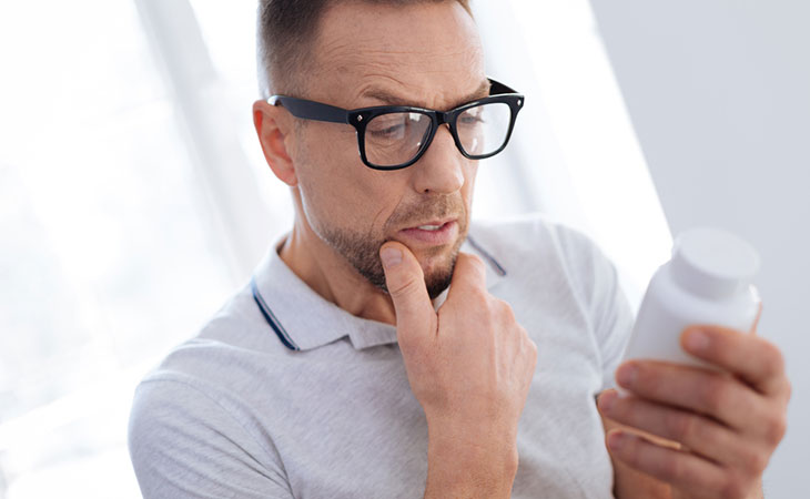 Man Thoughtful About Taking BCAA Protein Supplements