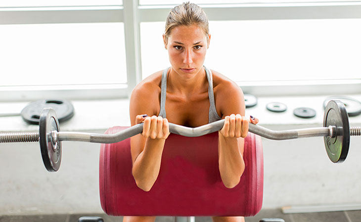 Woman Working Out Using An EZ Curl Bar
