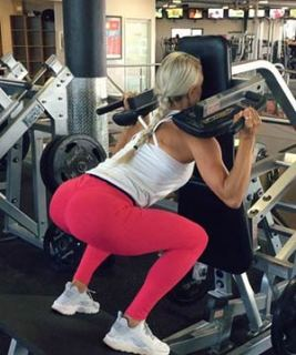 Woman Showing How To Reverse Hack Squat