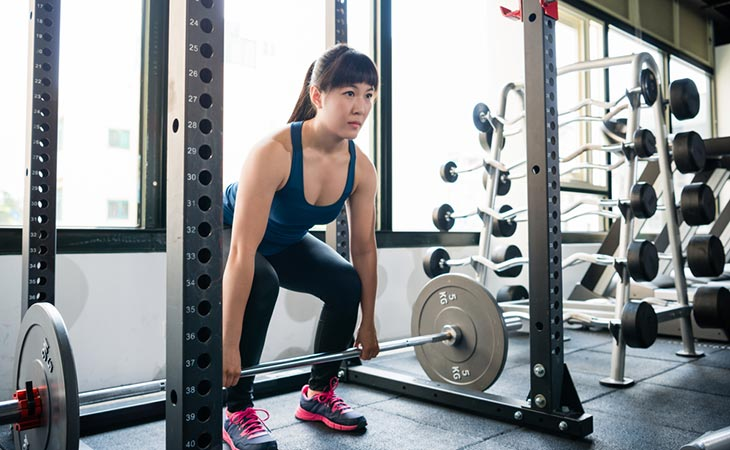 Woman Working Out Smith Machine Deadlift