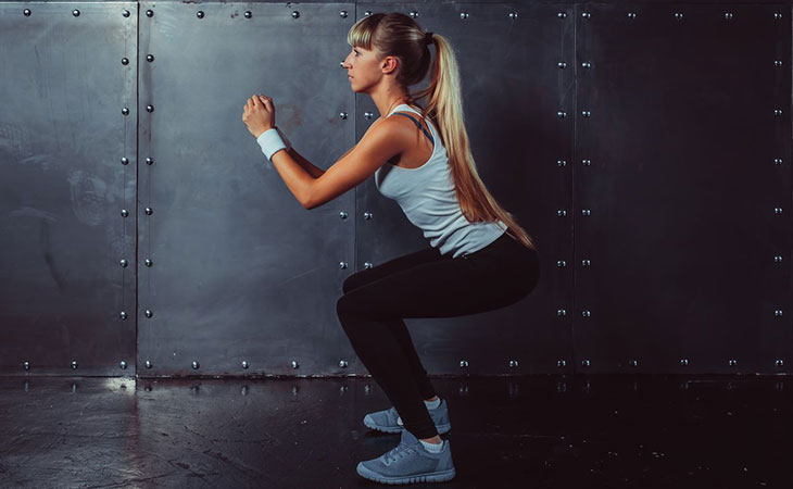 Woman Working Out Squatting For Legs Fitness