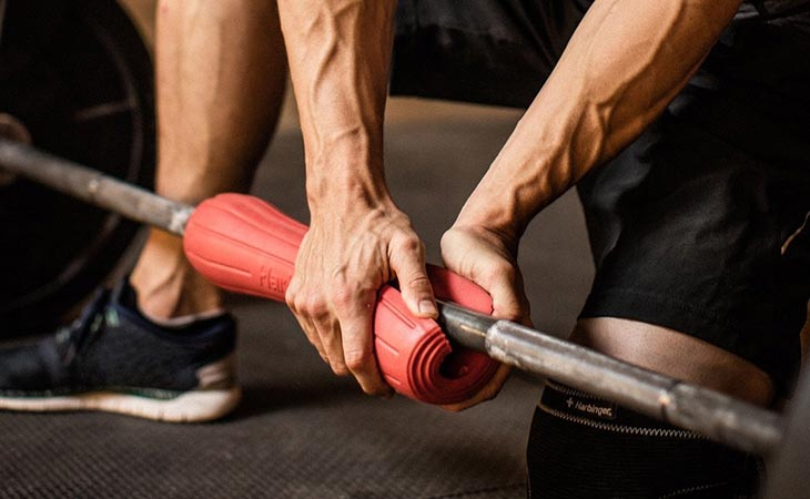 Man Adding Barbell Pad in His Barbell
