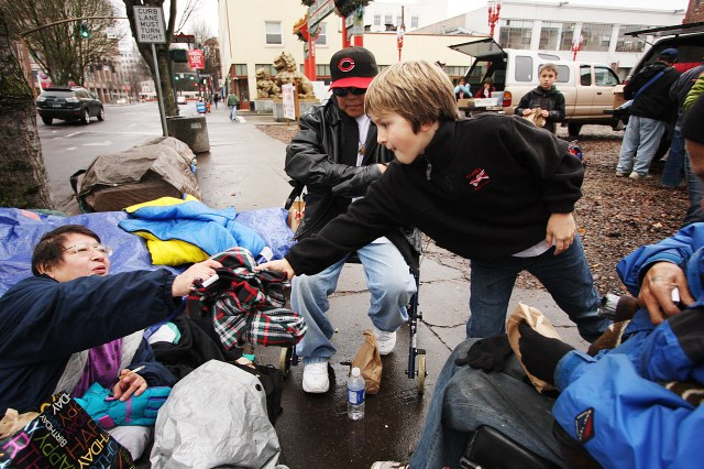 Carson Kelso, 10, gives lunches and blankets to Corrina Eastman, left, and Merris Wallulatun on West Burnside Street in Portland on December 19, 2009. Andrea J. Wright / for The Columbian