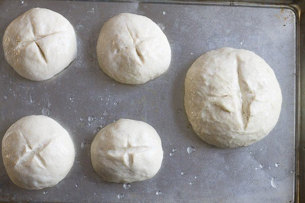 unbaked bread bowls on a sheet pan,