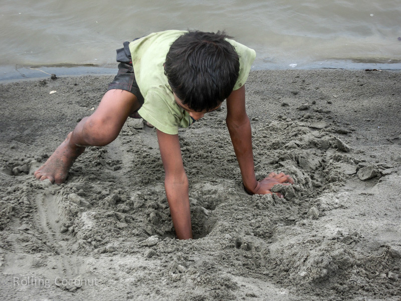 Bangladesh Cox's Bazar Inani Beach Kid Digging Crabs in Sand ooaworld Rolling Coconut Photo Ooaworld