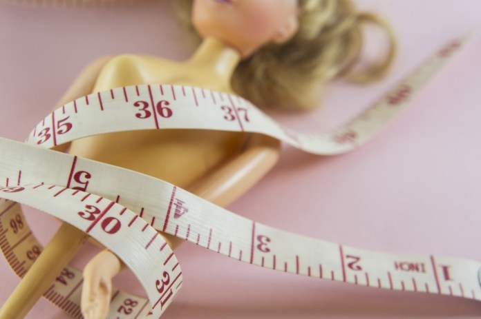 closeup measuring tape with women plastic doll on pink background