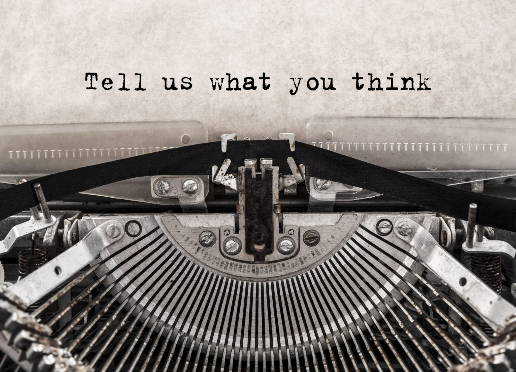 Vintage type writer with message 'tell us what you think' written on the inserted page