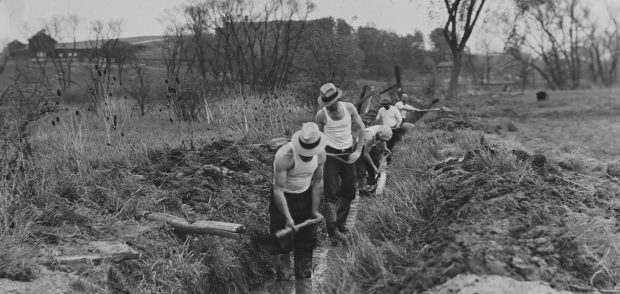 Workers for the Civilian Conservation Corps clear a drainage ditch, circa 1930s. AP Photo