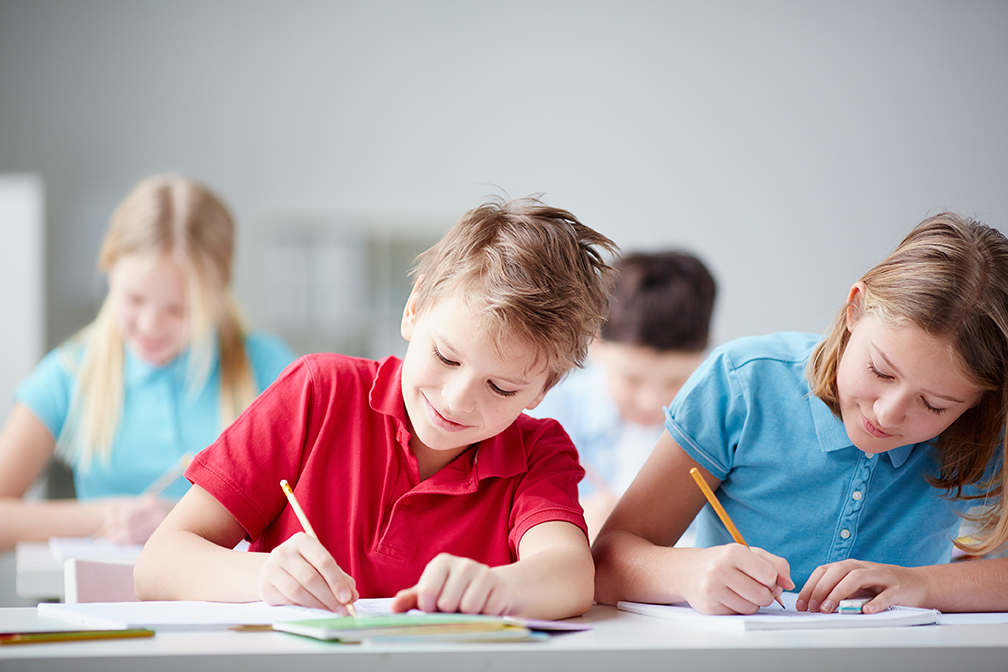 Portrait of two diligent pupils drawing at lesson