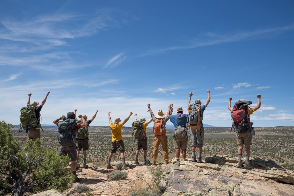 A group of adolescent students at Open Sky Wilderness Therapy face aways from the camera as they stand on a rocky outcropping with their arms raised in the air.