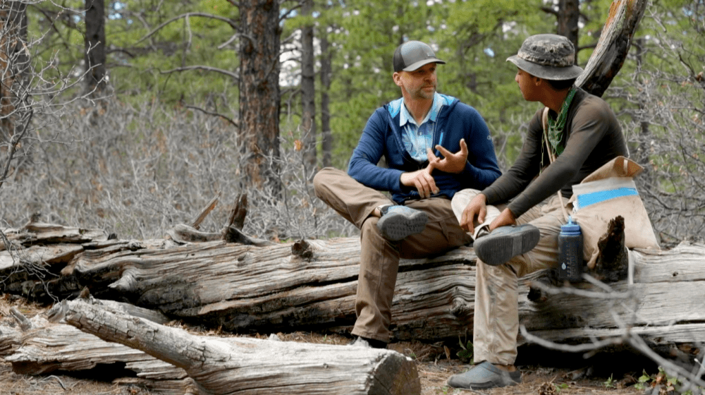 Clinical director and therapist Sebastiaan Zuidweg speaks with an Open Sky Wilderness Therapy student wile sitting on log.