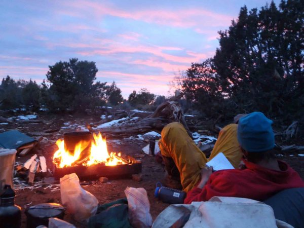A student sits by the fire he built during his solo experience in wilderness.