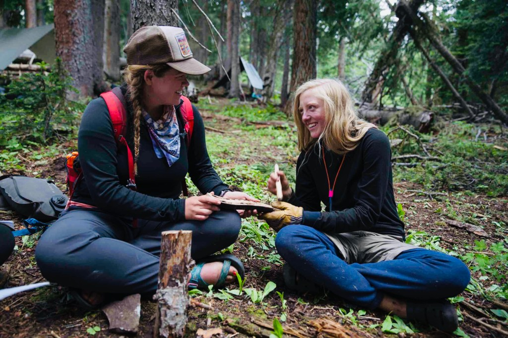 An Open Sky Wilderness Therapy field guide teachers a student how to bow drill a fire.
