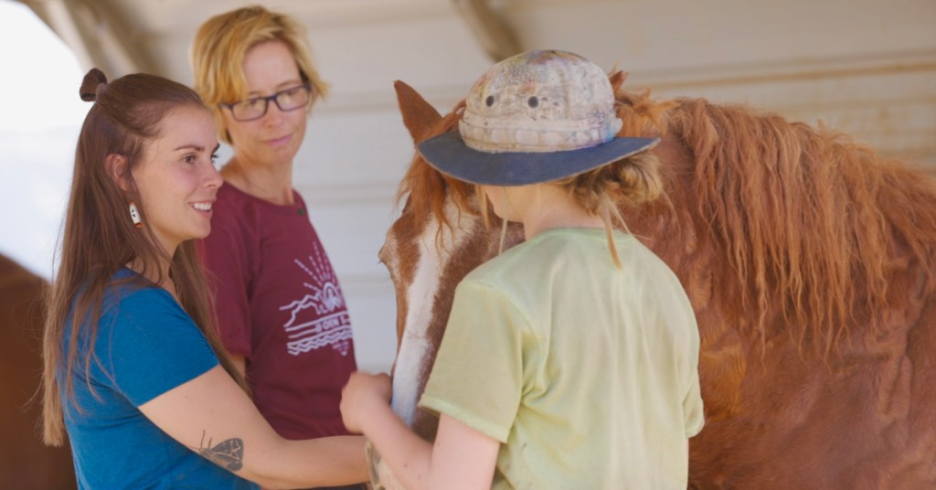 Clinical therapist Julia Lehr and early adolescent program director Liz Lucarelli pet a horse with an Open Sky Wilderness Therapy student at Medicine Horse Center.