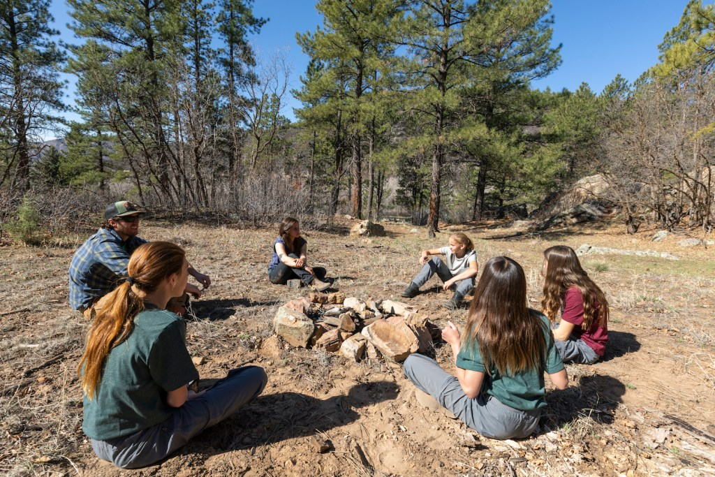 A group of early adolescent girls at Open Sky Wilderness Therapy participate in a group therapy session.