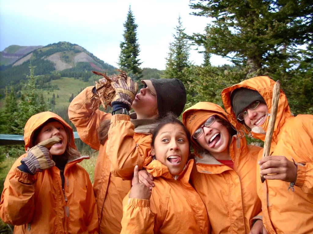 A group of adolescent girls wearing orange coats smile and act silly at Open Sky Wilderness Therapy.