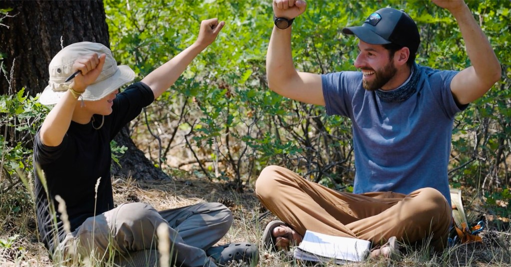 Clinical therapist Mark Sobel and a pre-teen student at Open Sky Wilderness Therapy smile and raise their hands above their heads..