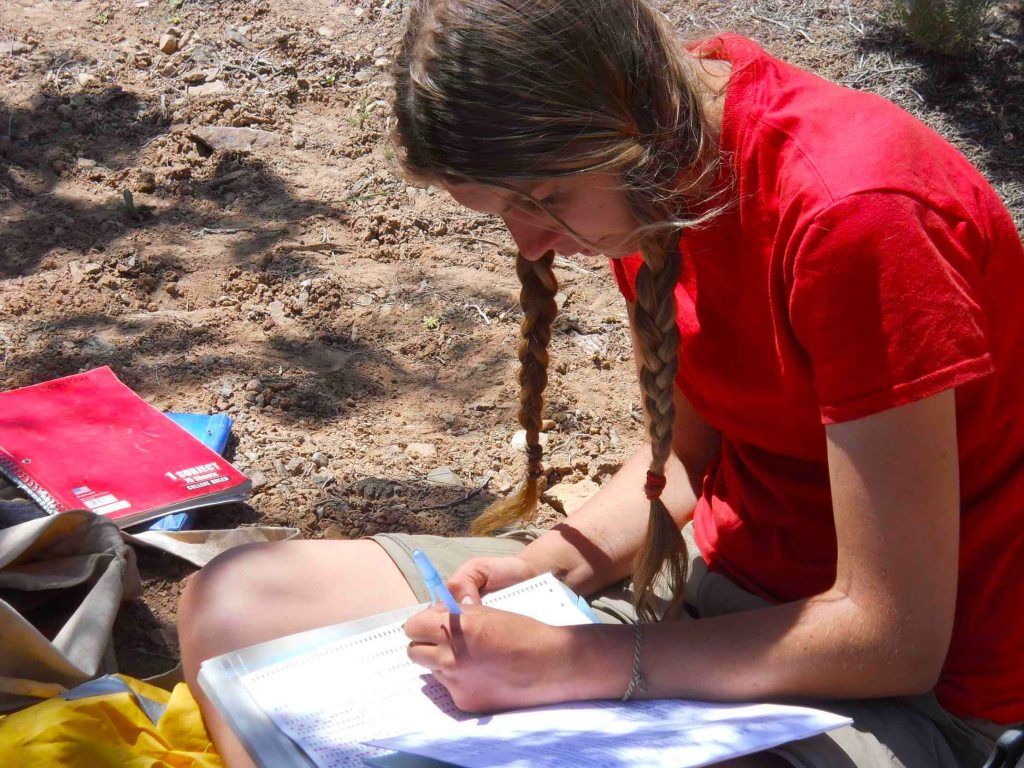 A student at Open Sky Wilderness Therapy sits and writes in a notebook.